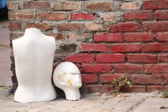 Decapitated Mannequin. The top half of a retired mannequin with the head on the ground by a brick wall Stock Photography