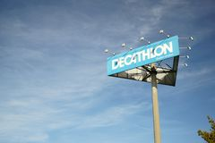 Decathlon Group signpost Germany Copy space sunlight. A signpost of the Decathlon Group on a sky background. Sunlight, copy space. French sporting goods retailer stock photos