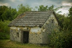Decay, decline, ruins. Village with abandoned building. House barrack in yard on natural landscape. Rural lifestyle, countryside. Architecture, structure stock image