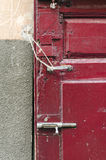 Decayed Door Lock. An old red door with a lock wich is complete disorder Stock Images