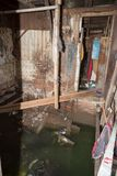 Decayed and flooded slum house. Slum house in Jakarta. The slums start at the foot of the tall skyscrapers with luxury apartments royalty free stock photography