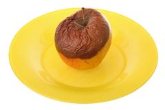 Decaying apple. On a plate. Isolated stock photo