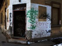 Abstract of Urban Decay. Decaying building and bankrupt store in urban environment with rusty door, broken windows and graffity Royalty Free Stock Photography