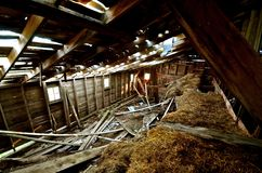 Decaying Hay Loft of a Barn. The entire barn is crumbling and decaying, from the foundation to the roof where the sun is steaming through Stock Image
