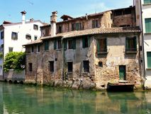 A decaying historic building beside a flowwing river in Treviso stock image
