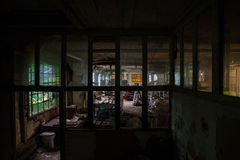 Decaying industrial building. Interior of a decaying industrial building viewed through bars Royalty Free Stock Photos