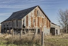 Decaying and rusting barn in a rural area. A decaying and rusting barn in a rural field behind fence stock photo