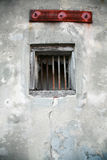 Decaying Window and Wall. A small square barred window with a wood frame peers out through a decaying concrete wall royalty free stock photography