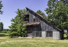 A decaying wooden barn on a beautiful day. A barn that has seen better days continues it`s slow trip to obscurity royalty free stock photos
