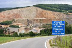 Decelerating sign. Warning Sign at the entrance road to a open quarry in mountain of the Belgian Ardennes Royalty Free Stock Photography