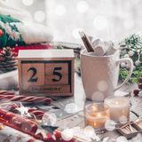 25 December Calendar. Christmas decor: Warm sweater, cup of hot cocoa with marshmallow, candy, candles and Christmas tree. Winter royalty free stock photos