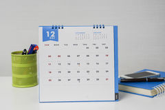 December calendar with stationary box and notebook on businesswoman desk Stock Photo