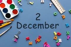 2 december Dag 2 van december-maand Kalender op zakenman of schoolkindwerkplaatsachtergrond Bloem in de sneeuw Stock Afbeeldingen
