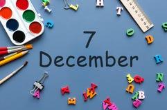 7 december Dag 7 van december-maand Kalender op zakenman of schoolkindwerkplaatsachtergrond Bloem in de sneeuw Stock Afbeeldingen