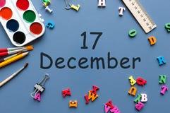 17 december Dag 17 van december-maand Kalender op zakenman of schoolkindwerkplaatsachtergrond Bloem in de sneeuw Stock Foto's