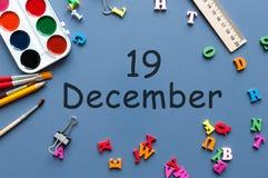 19 december Dag 19 van december-maand Kalender op zakenman of schoolkindwerkplaatsachtergrond Bloem in de sneeuw Stock Foto's
