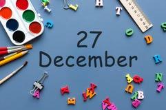 27 december Dag 27 van december-maand Kalender op zakenman of schoolkindwerkplaatsachtergrond Bloem in de sneeuw Stock Fotografie