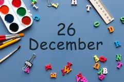 26 december Dag 26 van december-maand Kalender op zakenman of schoolkindwerkplaatsachtergrond Bloem in de sneeuw Stock Foto's