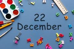 22 december Dag 22 van december-maand Kalender op zakenman of schoolkindwerkplaatsachtergrond Bloem in de sneeuw Royalty-vrije Stock Afbeeldingen