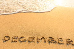 December - drawn by hand on a sandy sea beach. Royalty Free Stock Photography