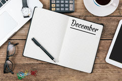 December; English month name on paper note pad at office desk. December, English month name on notepad, office desk with electronic devices, computer and paper stock photos