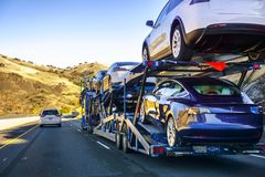 December 2, 2018 Gilroy / CA / USA - Car transporter carries Tesla Model 3 new vehicles along the highway, back view of the trail. Er royalty free stock photography