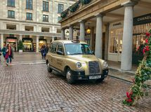 Gold taxi painted with Gabrielle Chanel outside the Chanel shop in Covent Garden, London royalty free stock photos