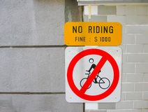 December 24, 2008: ` Inget ridning`-tecken på en gata i Singapore Arkivbild