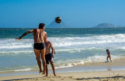 6 December 2016. Jumping man playing beach football on the background of Atlantic ocean at Copacabana beach Royalty Free Stock Photos