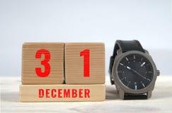 31 december, kalender op houten blokken met horloge Stock Foto