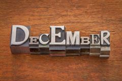 December month in metal type. December word in mixed vintage metal type printing blocks over grunge wood with a digital painting filter applied stock image