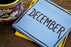 December, reminder note with coffee. December, - handwriting in black ink on a  sticky note with a cup of coffee Royalty Free Stock Photos