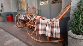 Wicker cozy armchair with blanket and small glass table outdoors. Plaid lies on the wicker furniture from rattan. stock photos