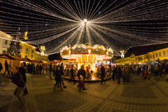 24 December 2014 SIBIU, ROMANIA. Christmas lights, Christmas fair, mood and people walking. Fish eye lens effects royalty free stock photo