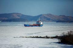 A large container ship is on the roadstead in a frozen bay near the village of Slavyanka in the Primorsky Krai. stock images