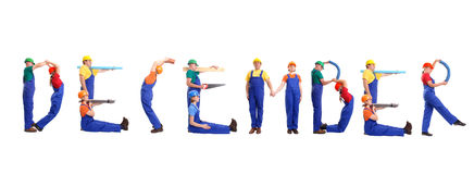 December staff. Group of young people wearing different color uniforms and hard hats forming December word - isolated on white background - calendar concept Royalty Free Stock Photo