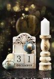 31 December träkalender, tappningjulbollar och antik klocka arkivbild
