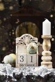 31 December träkalender, tappningjulbollar och antik klocka arkivbilder