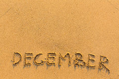 December - word inscription on the gold sand beach. Royalty Free Stock Photos