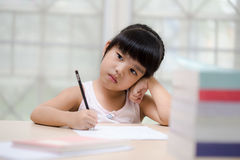 Decent school child. holding her head with a hand and reading a book Stock Images
