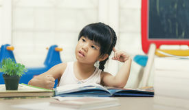 Decent school child. holding her head with a hand and reading a book.  Stock Images