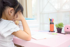Decent school child. holding her head with a hand and reading a book.  Royalty Free Stock Photos