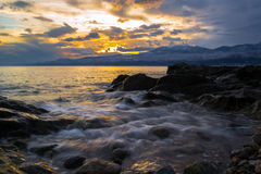 A decent Wave. Decent Wave at Beach in Rijeka, and Golden colored Sky above Adriatic Sea along The Coast and Mountains above The Cityes, Croatia, photographed at Stock Image