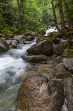 Deception Falls, Skykomish, Washington. Deception Creek crashes down a few steps, then glides over smooth rock under the highway and ends in a square, misty royalty free stock image