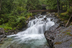 Deception Falls, Skykomish, Washington. Deception Creek crashes down a few steps, then glides over smooth rock under the highway and ends in a square, misty stock image