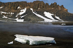 Deception Island - Antarctica. Melting iceberg on the shores of Whalers Bay, Deception Island, Antarctica with the sulfur gas seeping from the active volcano stock photography