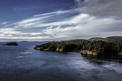 Deception Pass. View of Deception Pass from the bridge with blue sky and water and foreground fall trees Stock Photo