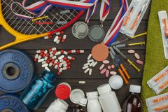 Deception in sports. Doping for athletes. Scammers in the sport. Abuse of anabolic steroids for sports. Anabolic steroids spilled on a wooden table. Fraud in Royalty Free Stock Image