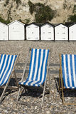 Dech Chairs and Beach Huts at Beer, Devon, UK. Blue and white striped deck chairs and beach huts on the beach at Beer, Devon, UK Royalty Free Stock Photos