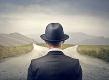 Decide. Businessman with hat in front of two deserted roads